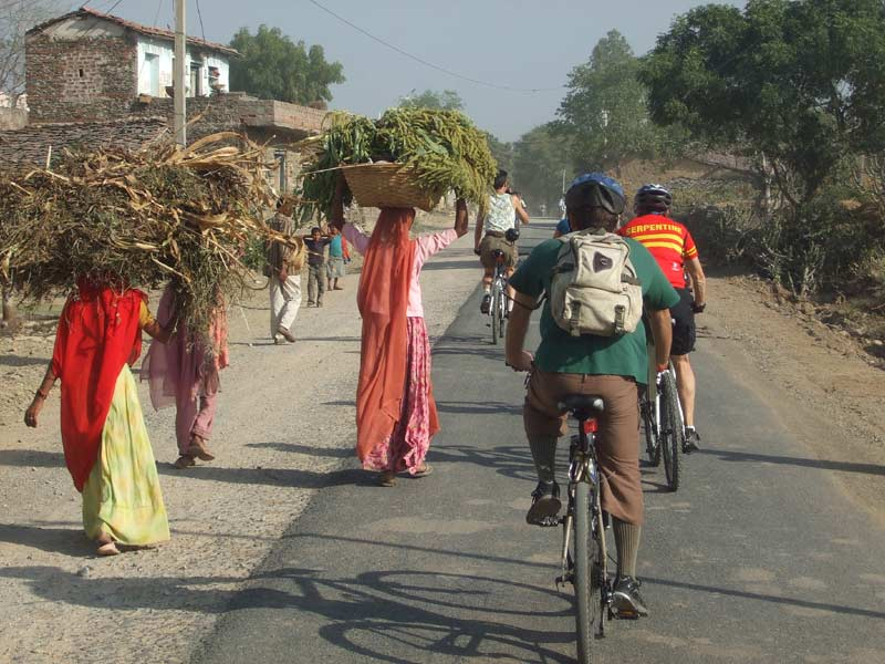 Cyclists passing through country village, Rajasthan