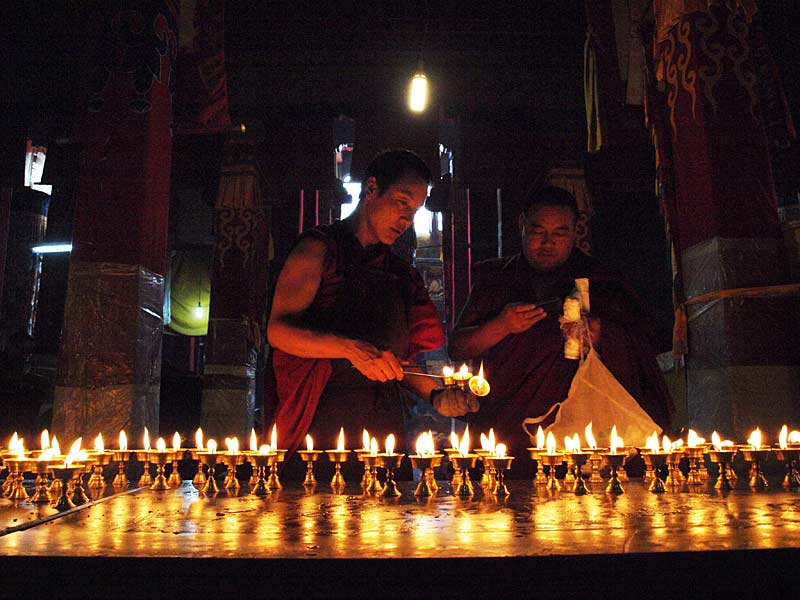 Lighting butter lamps inside the Jokhang Temple