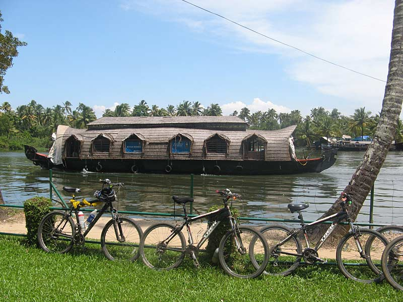 Bikes on the canalside, houseboat in kerala