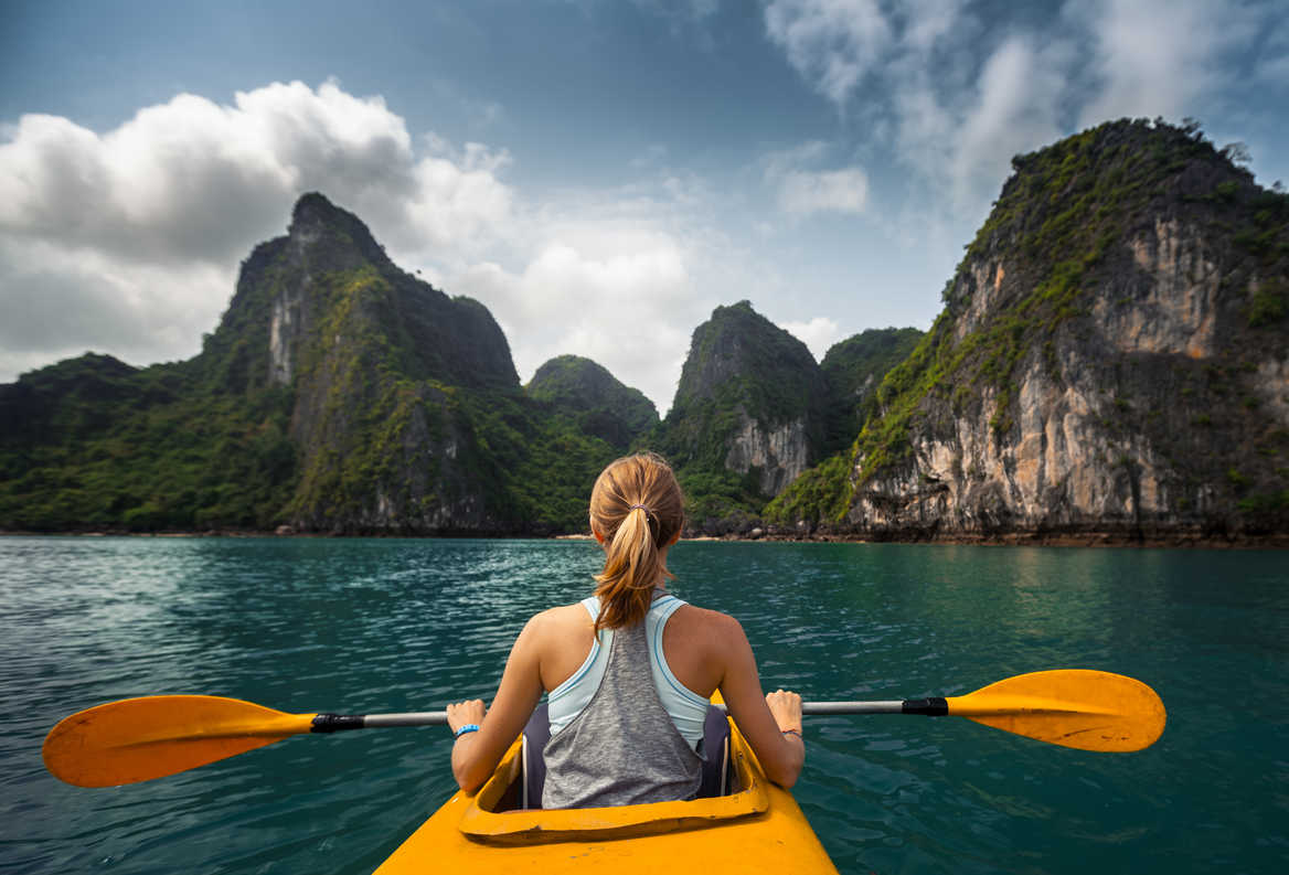 Woman exploring Ha Long Bay, Vietnam by kayak.