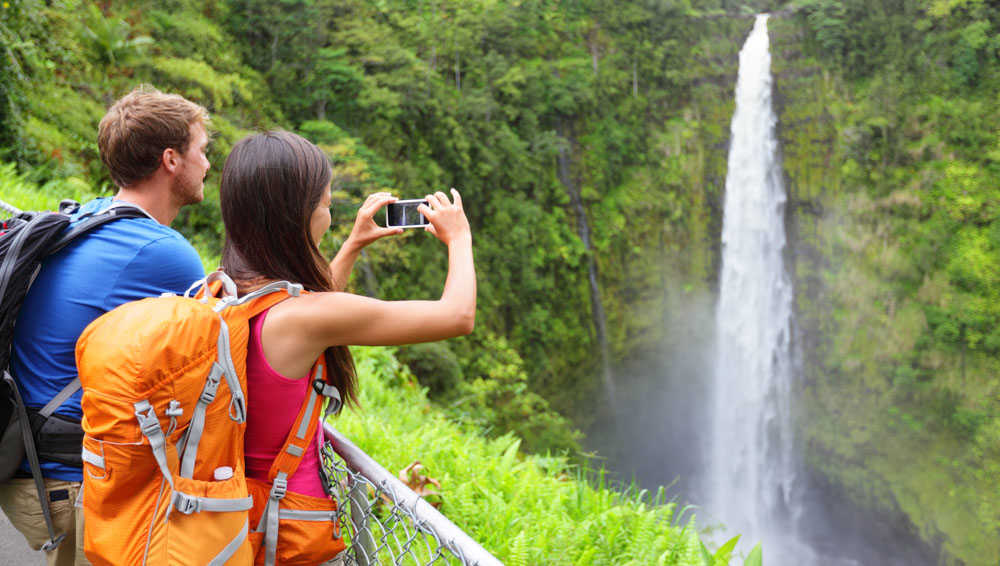 Couple taking photo of Waterfall Hawaii