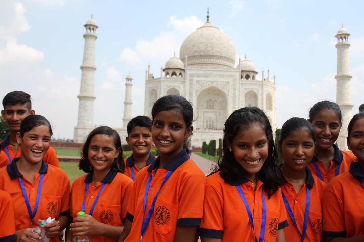Children smiling at Taj Mahal
