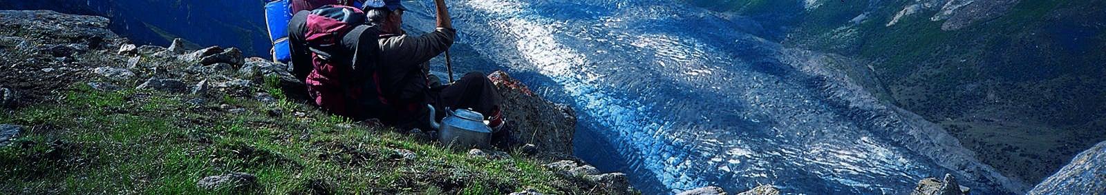 Trekker and porter resting during climb to Rash Lake