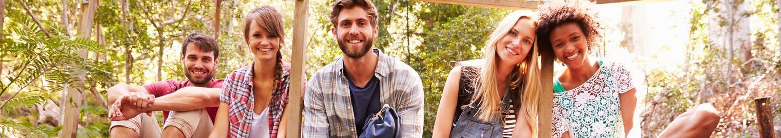 friends sat on a wooden bridge in forest