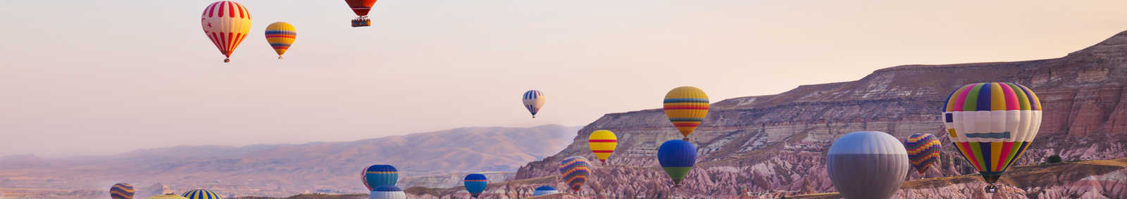 Hot air balloon flying over rock landscape at Cappadocia, Turkey