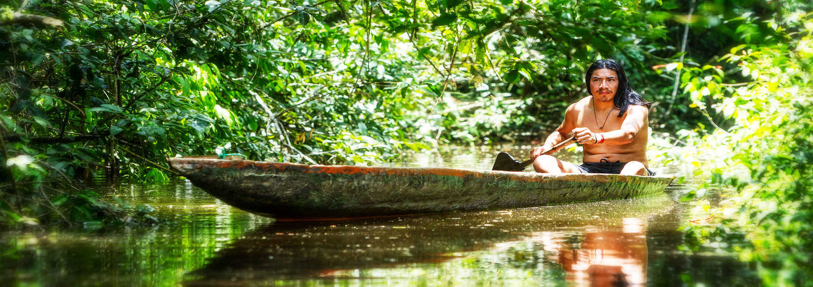 Indigenous man canoeing through the Amazon jungle, Ecuador