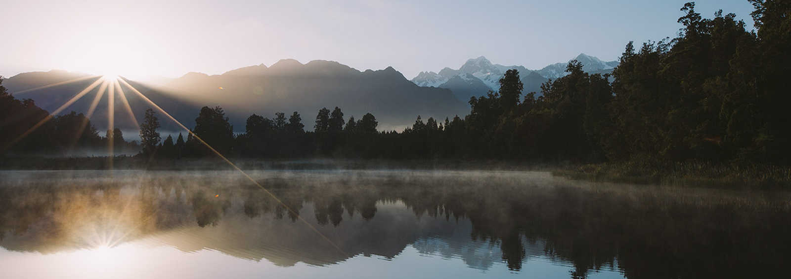 West Coast - sunrise over the Southern Alps from Lake Matheson, New Zealand