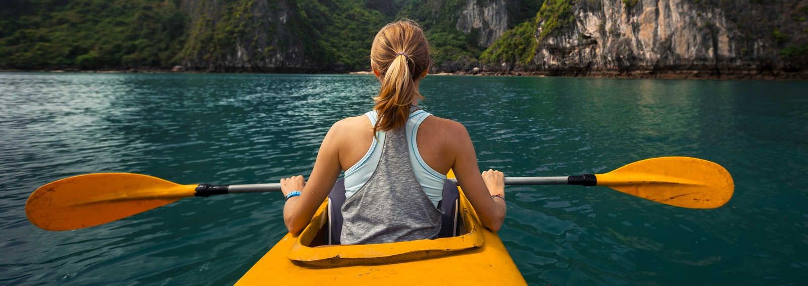 Woman exploring calm tropical bay with limestone mountains by kayak. Ha Long Bay, Vietnam