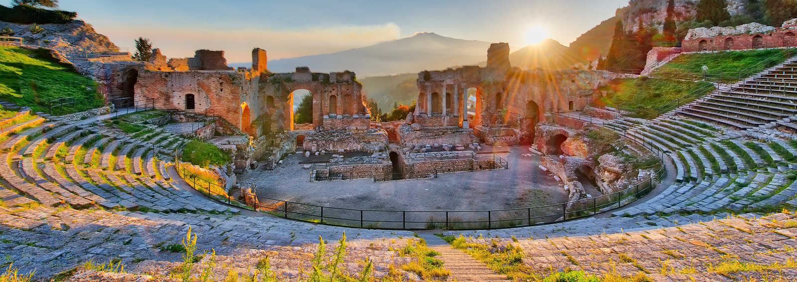 Ancient theatre of Taormina, Siciliy, Italy with Etna erupting volcano at sunset