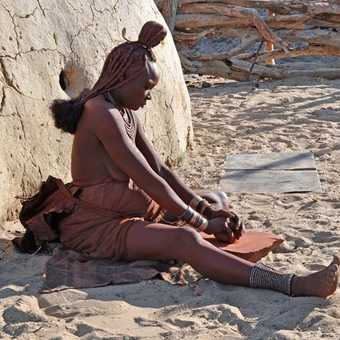 Himba woman grinding red ochre