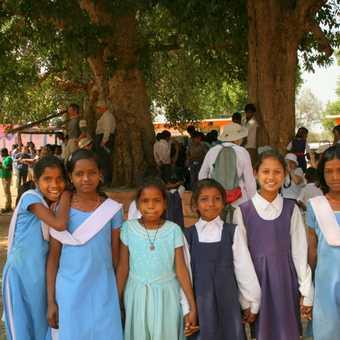 The girls in their school uniforms enjoy the cricket match event