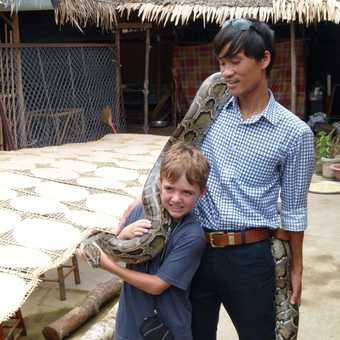 Holding a python with the help of our guide Quan