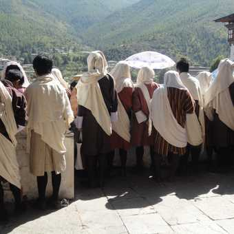 MEN IN NATIONAL DRESS WATCH THE FESTIVITIES