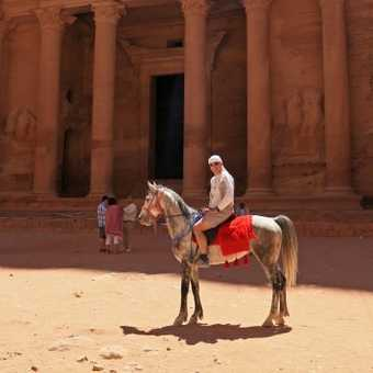 Astride a grey Arab stallion in front of Petra's Teasury