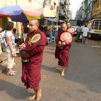 3 monks with alms bowls in a busy street in Yangon