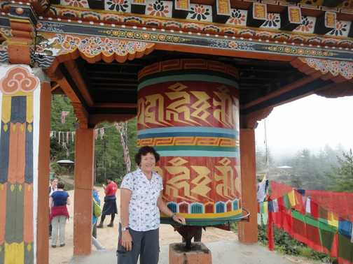 BY A LARGE PRAYER WHEEL, ON THE WAY TO THE TIGER'S NEST