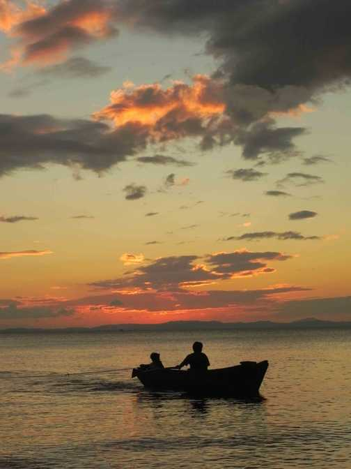 Local boys fishing in lake Nicargua at sunset