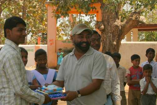 Balvinder giving gifts for the children to a teacher at the local school