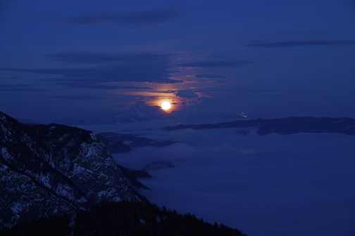 Moon rising over Bohinj valley viewed from mountain hut