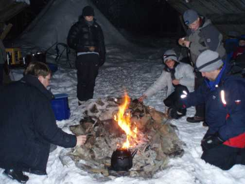 Toasting marshmallows at night, by teepees