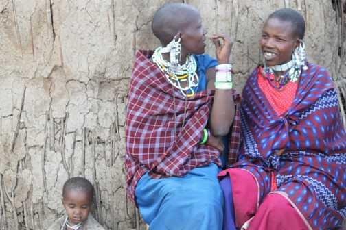 Masai women and child sitting by their manyatta