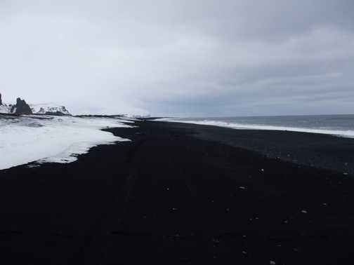 White snow on black sand beach
