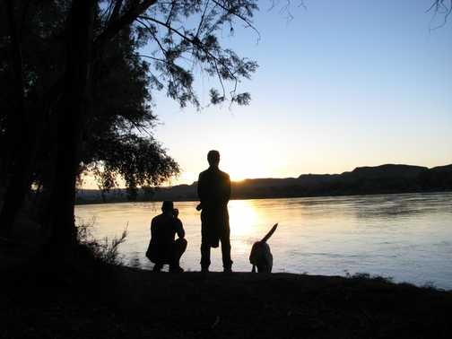 Two guys and a dog Sunset Orange River, Namibia,