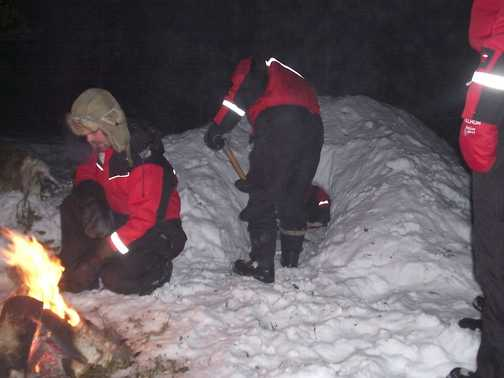 Excavating inside of igloo by campfire