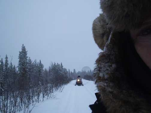 My ice encrusted hat, following snowmobiles and satellite dish in the distance