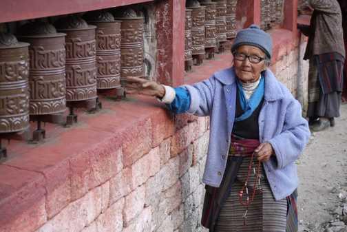 Nepalese lady at prayer wheel NAMCHE BAZAAR