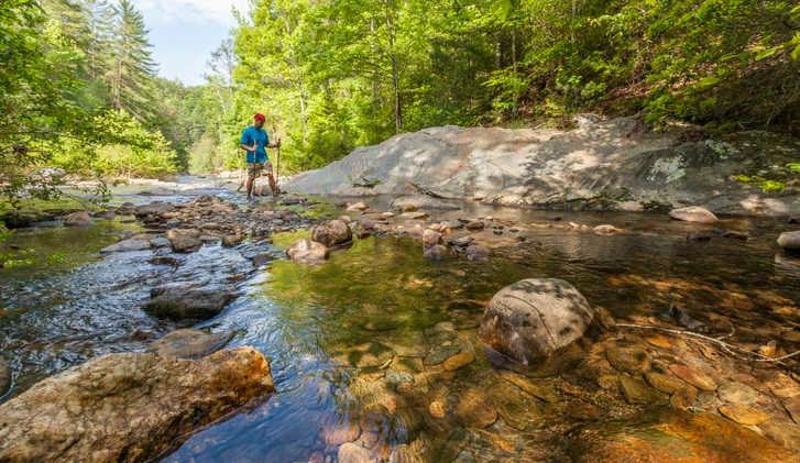 A hiker crossing a rocky mountain stream